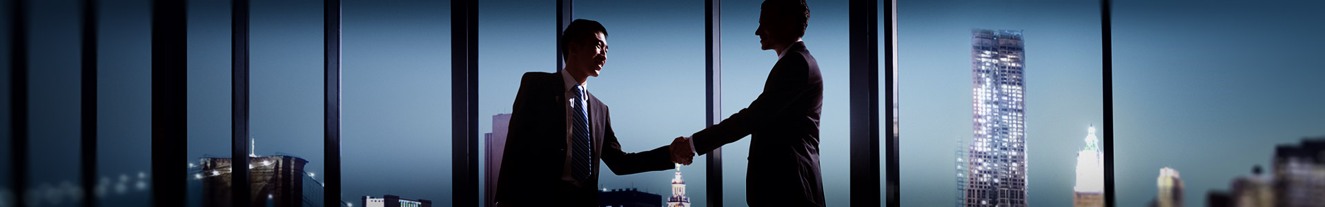 two businessmen shaking hands together at a desk in a office in business skyscraper