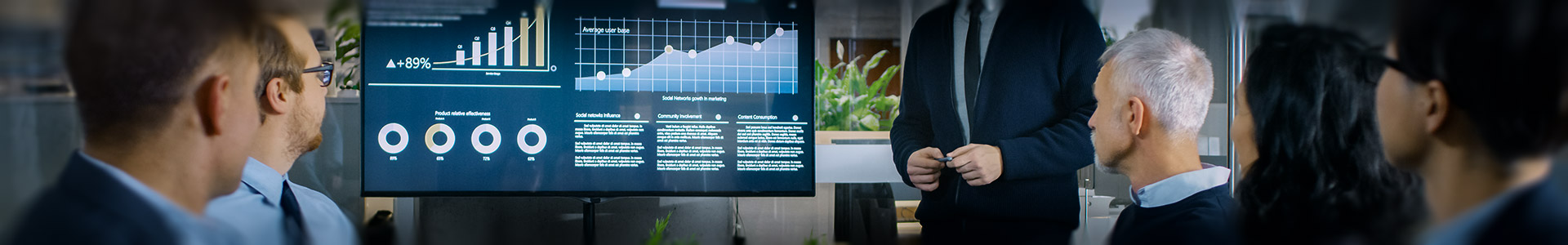 group of financial professionals having a meeting looking at a screen with financial graphs